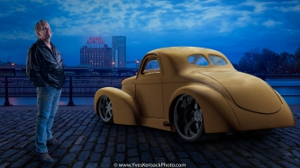 A proud owner of a hotrod car poses in Old Montreal at sunset