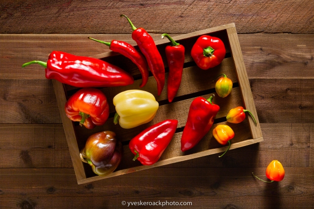Assortment of peppers in a wood crate on a textured dark wood planks background